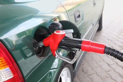 Red pump for refueling filling green car Stock Images