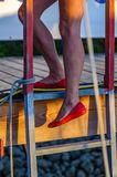 Red pumps on a ladder stock image