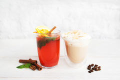 Red punch and latte in glasses on white background stock images