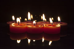 Red and purple candles on black background stock photography