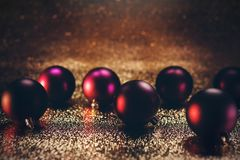 Red and purple Christmas baubles. Dark red shiny Christmas balls laying on festive golden fabric with some bokeh in background Royalty Free Stock Photos