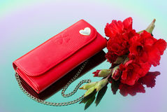 Red purse with chain and red gladiolus. Are reflected in the color mirror Stock Images