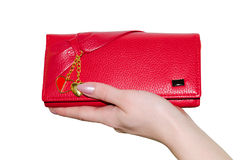 Red purse. Red purse in a female hand isolated on white background Royalty Free Stock Image