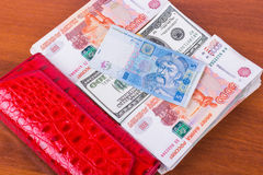 Red purse, wads of money and 5 hryvnia on wooden background Stock Photo
