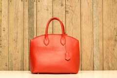 Red purse on wood background. Luxury women accessory Royalty Free Stock Photo