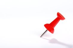 Red push pin. Stuck in sheet of paper Stock Image