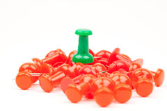 Red push pins with a green push pin standing out Royalty Free Stock Photography