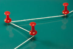 Red push pins. Thumbtacks red and white wire on green background Royalty Free Stock Photos