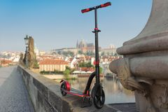 Red push scooters against the backdrop of the Charles Bridge in the Prague, Czech Republic. Horizontal royalty free stock photo