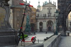Red push scooters against the backdrop of the St.Salvator Church in the Prague, Czech Republic. Horizontal stock photography