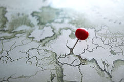 Red pushpin on a map. Pushpin marking location on a geography map Royalty Free Stock Photo