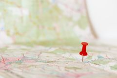 Red pushpin marking a location on an open map. Single red pushpin marking a location on an open map Royalty Free Stock Photos