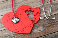Red puzzle heart. With stethoscope on grey wooden background Stock Photo