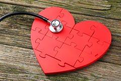 Red puzzle heart. With stethoscope on wooden background Stock Photo