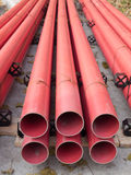 Red PVC Pipes. Stacked red PVC pipes to be used in a construction project stock photos