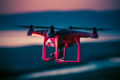 Red quadcopter flying in the dark sky. Red quadcopter flying over the sea on the background of dark evening sky Royalty Free Stock Photo