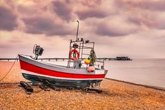 Red quaint, traditional fishing boat moored on the pebble shingle beach in Deal, Kent, UK with the pier in the background. On a clouds winter day stock images