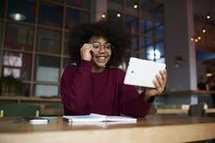 Red que practica surf de la muchacha del inconformista vía el panel táctil moderno que aprende en biblioteca con la conexión del  Fotografía de archivo libre de regalías