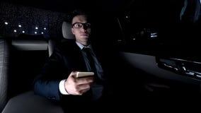 Red que practica surf del hombre de negocios cansado en smartphone, montando en el coche, analizando proyecto imagen de archivo
