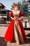 Red Queen in the castle. Red-haired woman in a chic vintage dress. Fashion Photo royalty free stock photos