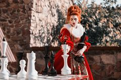Red Queen in the castle. Red-haired woman in a chic vintage dress. The Red Queen is playing chess. Red-haired woman in a chic vintage dress. Fashion Photo Royalty Free Stock Photography