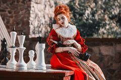 Beautiful girl with red hair. The Red Queen is playing chess. Red-haired woman in a chic vintage dress. Fashion Photo royalty free stock images