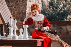 Red Queen in the castle. Red-haired woman in a chic vintage dress. The Red Queen is playing chess. Red-haired woman in a chic vintage dress. Fashion Photo Royalty Free Stock Photo