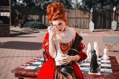 Charming girl with red hair. The Red Queen is playing chess. Red-haired woman in a chic vintage dress. Fashion Photo stock images