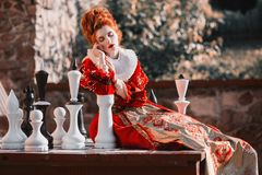 Red Queen in the castle. Red-haired woman in a chic vintage dress. The Red Queen is playing chess. Red-haired woman in a chic vintage dress. Fashion Photo Stock Photography
