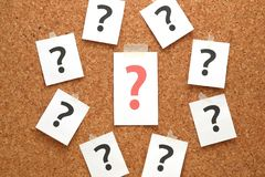 Red question mark on a piece of paper and many question marks on cork board. Question concept stock images