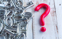 Red question mark and silver keys on wooden table stock photos