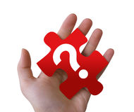Red Question Puzzle Piece. An isolated, Caucasian hand is holding a red puzzle piece with a question mark on it Royalty Free Stock Image
