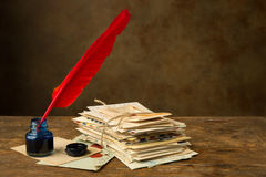 Red quill feather and old letters Royalty Free Stock Photography