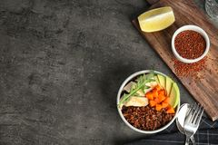 Red quinoa with garnish in bowl on table, top view. Space for text stock image