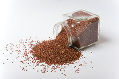 Red Quinoa. In a glass jar on a white background Stock Image