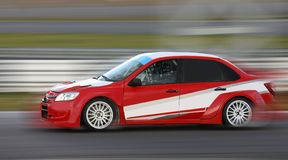 Red race car racing on race track. Red race car racing at high speed on race track with motion blur stock photography
