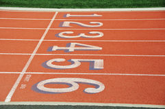 Red race track with numbers. Photo Lanes of a red race track with numbers and green football field Stock Images