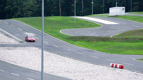 Red racing car speeding and turning on a race-track. Vehicles drive on rough terrain, through obstacles and in extreme weather conditions to practice driving stock video footage