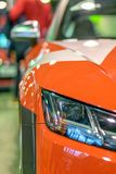 Front headlight of a sports racing red car, on autoexhibition autobody. Red racing sports car shines and shimmers in the lights of the auto show stock photography