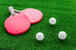 Red racket for ping pong ball green background close up Stock Photo