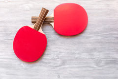 Red racket for ping pong ball wooden background top view Royalty Free Stock Photos