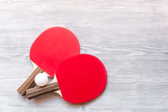 Red racket for ping pong ball wooden background top view Stock Photo