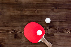 Red racket for ping pong ball wooden background top view Royalty Free Stock Photo