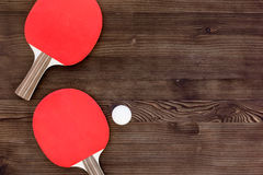 Red racket for ping pong ball wooden background top view Royalty Free Stock Photography