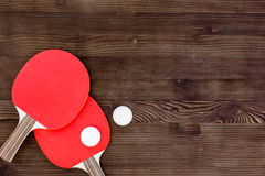 Red racket for ping pong ball wooden background top view Stock Images