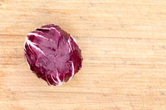 Red radicchio on a bamboo board. Overhead view of a single red radicchio rich in anthocyanin on a bamboo cutting board with copyspace stock image