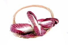 Red radicchio salad in a straw basket. Isolated on white Stock Image