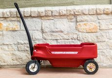 Red Radio Flyer wagon against a stone wall. Vintage plastic red Radio Flyer wagon against a limestone block wall Royalty Free Stock Images