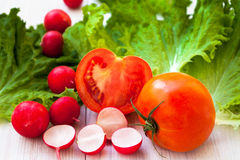 Red radish, lettuce and tomato. Healthy lettuce, red radish and juicy tomato on the table Royalty Free Stock Photo