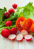 Red radish, lettuce and tomato. Organic lettuce, red radish and juicy tomato on the table Royalty Free Stock Photography